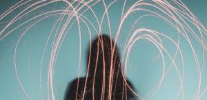 Woman marking sparkler design at dusk, light trails.